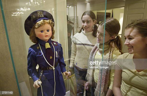 A group of girls look at a uniformed doll depicting a member of the Girl Guides of Canada given to Caroline Kennedy by the Girl Guides during...