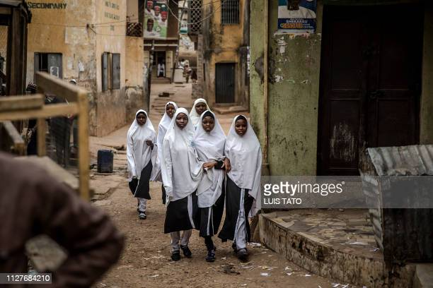 Group of girls observe people celebrate on February 27, 2019 in a street of Kano, the re-election of Muhammadu Buhari as Nigerian president after a...