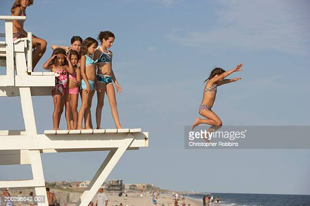 Group of girls (5-12) on life guard's platform, one jumping off