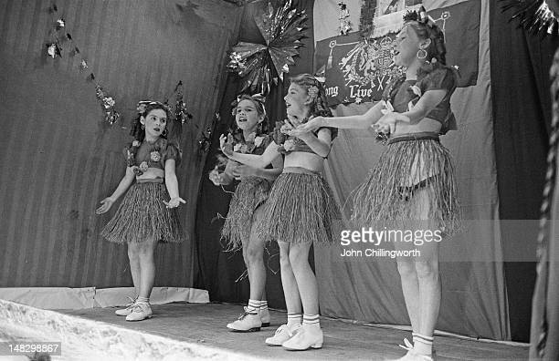 A group of girls performing a hula dance at a party to celebrate the coronation of Queen Elizabeth II held in Morpeth Street in London's East End 2nd...