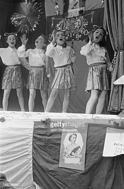A group of girls performing a song and dance routine at a party to celebrate the coronation of Queen Elizabeth II held in Morpeth Street in London's...