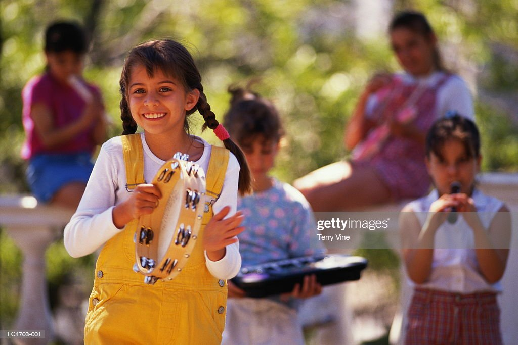 Group of girls (6-9) playing music in park : Stock Photo