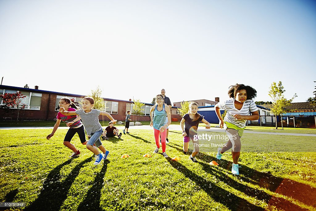 Group of girls running race during athletics class : Stock Photo