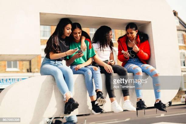 Group of girls sitting on city street