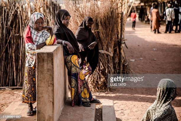 A group of girls stand in front of their compound at Malkohi refugee camp in Jimeta Adamawa State Nigeria on February 19 four days ahead of the...