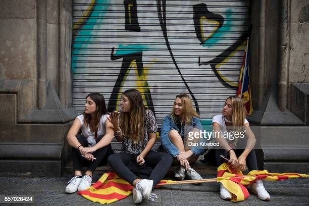 A group of girls take a break from a march in front of a closed shop during a regional general strike to protest against the violence that marred...