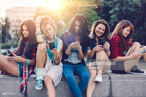 Group of girls texting on smartphones