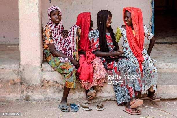 A group of girls wait for their families at a polling station at the Malkohi refugee camp in Jimeta Adamawa State on February 23 during the...