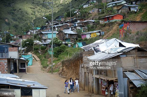 A group of girls walk along 'La Honda' shantytown where about 700 families displaced by the violence from different regions of the country live in...
