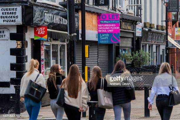 A group of girls walk past closed down shops in Bolton town centre as Coronavirus restrictions are tightened in the area on September 09 2020 in...
