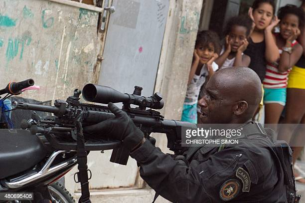 A group of girls watch how a PM paramilitary police BOPE special unit sniper secures the area as Brazilian soldiers conduct a search for weapons in...