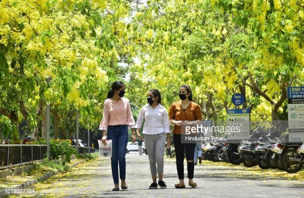 A group of girls wearing facemasks while walking along a road lined with Amaltas tree at the Guru Nanak Dev University campus on June 11 2020 in...