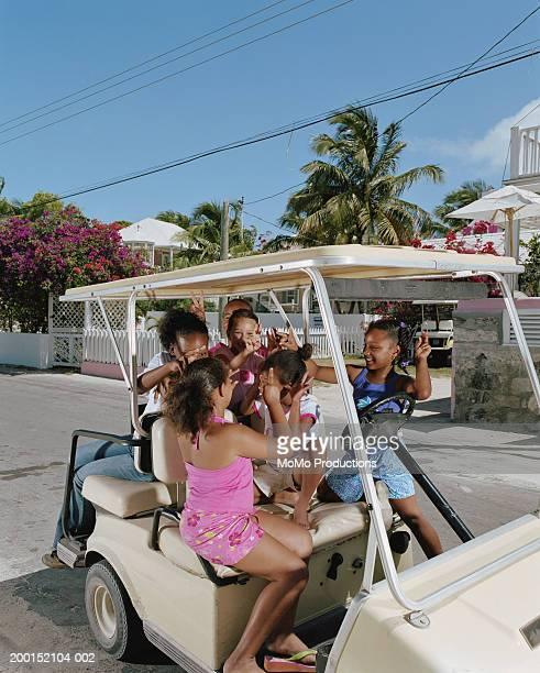 group of girls (10-12) with hands in air in golf cart, smiling - ハーバー島 ストックフォトと画像