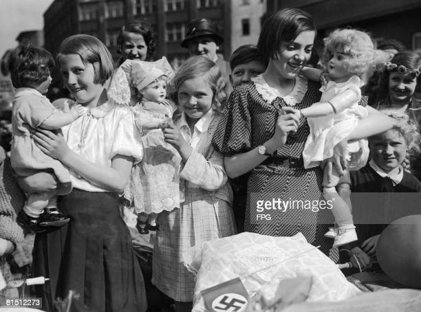 A group of girls with their dolls ready to take part in a Mothers' and Children's day procession in Berlin 8th April 1934 On the pram in the...