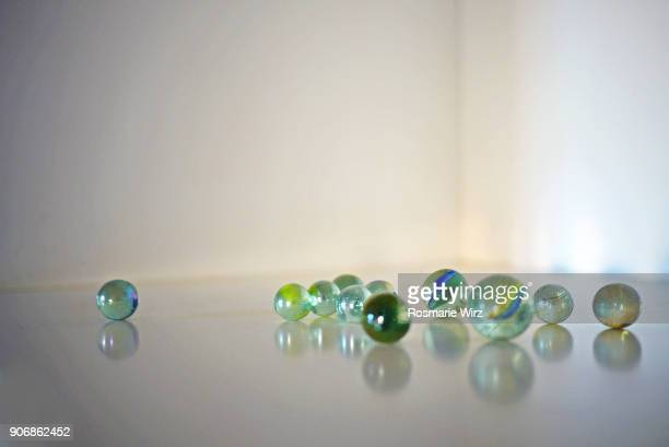 Group of glass marbles rolling on a reflecting surface