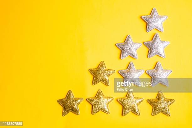 a group of golden and silver stars against yellow background - image stock pictures, royalty-free photos & images
