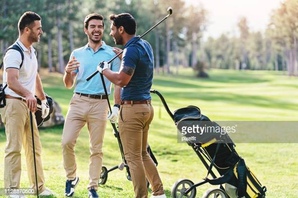 group of golf players talking and laughing - khaki trousers stock pictures, royalty-free photos & images