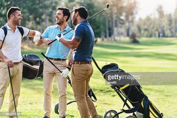 gruppe von golfern, die gute zeit miteinander haben - golf lustig stock-fotos und bilder
