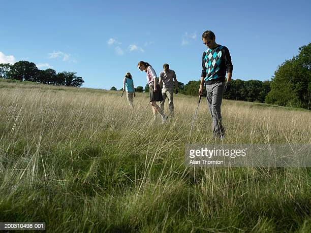 group of golfers looking in long grass, low angle view - searching stock pictures, royalty-free photos & images