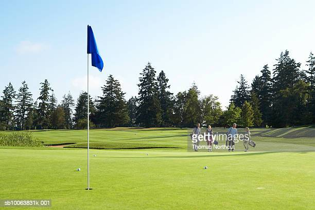 group of golfers walking towards putting green - golfer stock pictures, royalty-free photos & images