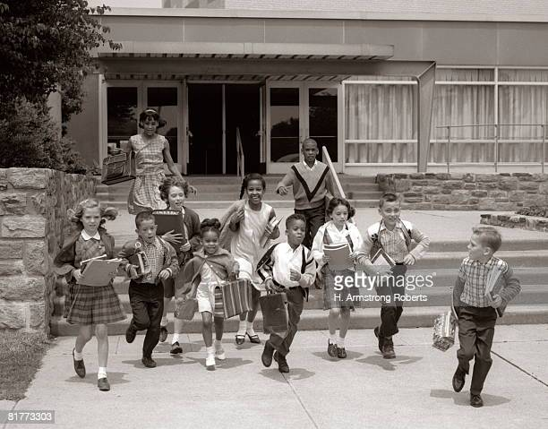 group of grade school children running down school stairs with books & bags. - 20th century stock pictures, royalty-free photos & images