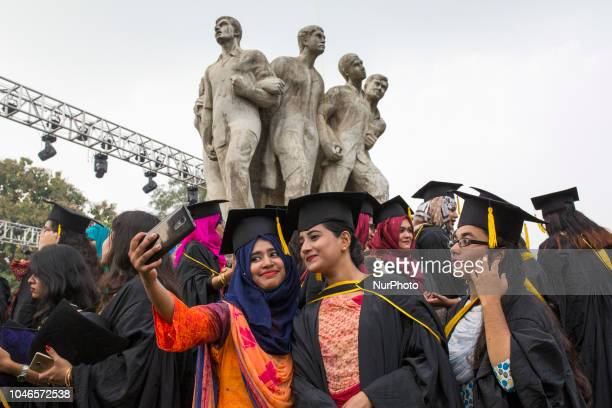 A group of graduates expressing their delight in front of the sculpture Raju at TSC area on the 51th convocation of the students of Dhaka University...