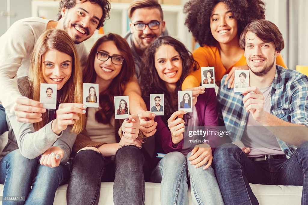 Group of graduates showing instant self portraits : Stock Photo