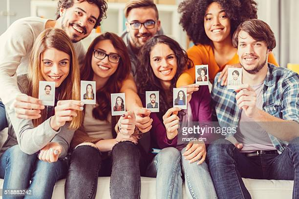 group of graduates showing instant self portraits - identity stock photos and pictures