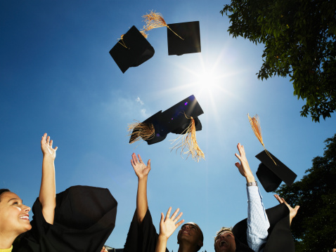 Group of graduates throwing mortar boards in air - gettyimageskorea