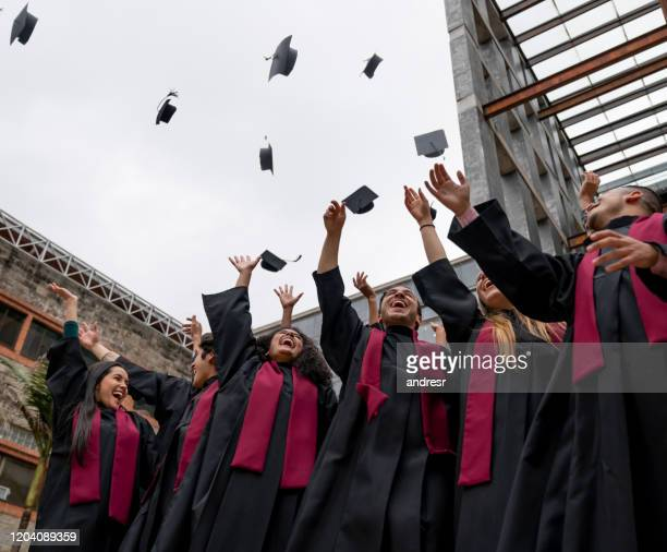 group of graduating students throwing their mortarboards in the air - alumni stock pictures, royalty-free photos & images