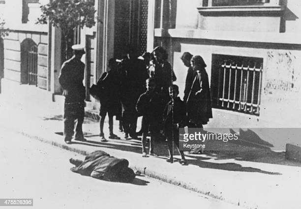 A group of Greek civilians by the body of a man who collapsed from hunger and died in an Athens street during the Great Famine the period of mass...