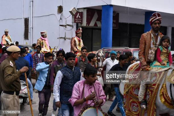 A group of grooms arrives for a ritual during a mass wedding for eight couples at Hanuman Vatika Ramleela Maidan on March 8 2019 in New Delhi India...