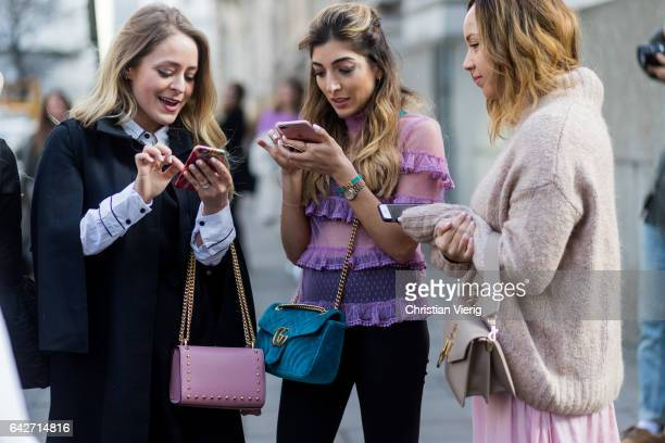 A group of guests on their phone texting and talking outside Julien Macdonald on day 2 of the London Fashion Week February 2017 collections on...