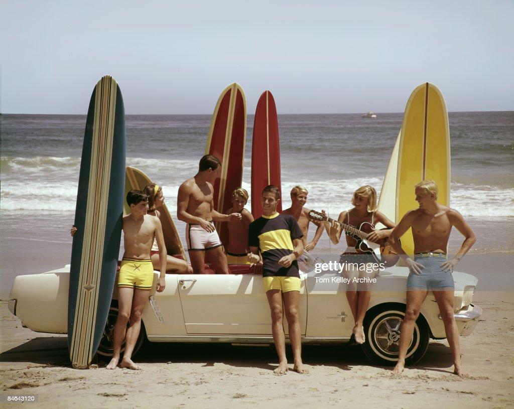 A group of guys and gals (and their surfboards) gather round an old Ford Mustang on the beach, 1964.