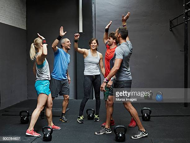 group of gymters celebrating workout - human arm stock pictures, royalty-free photos & images
