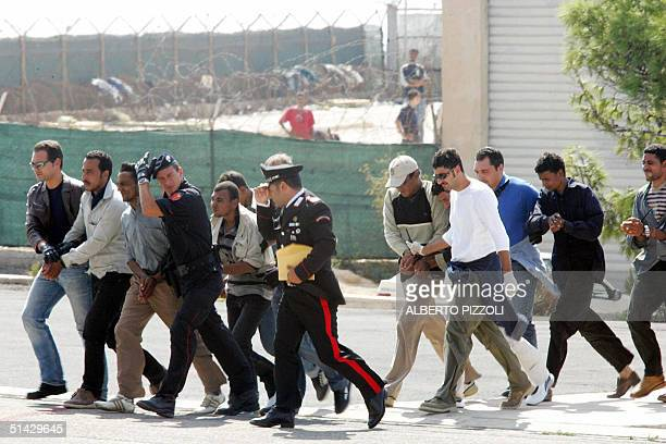 Group of handcuffed clandestine immigrants, are escorted by Italian Carabinieri from Lampedusa's reception centre 06 October 2004, to the civil...
