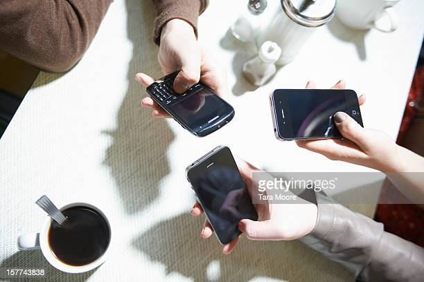 group of hands texting on mobiles in cafe