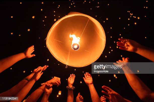 group of hands together releasing the flying lantern with numerous lanterns in the sky, yeepeng festival , chiangmai, thailand - releasing stock pictures, royalty-free photos & images