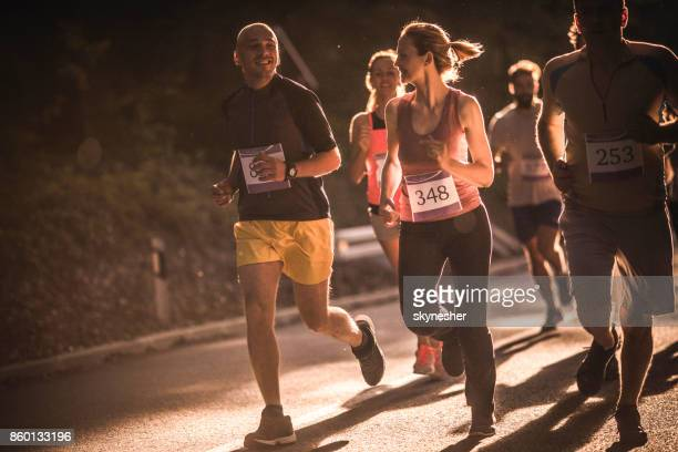 Group of happy athletes having a road running race in nature.