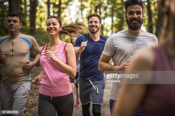 森の中、マラソンを実行して幸せな選手のグループ。 - ハーフマラソン ストックフォトと画像