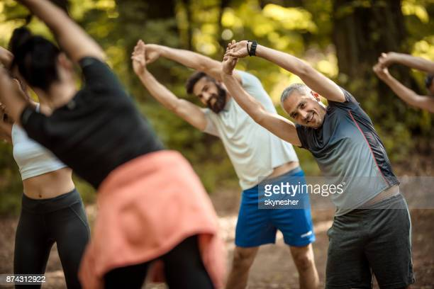 Group of happy athletes stretching their arms with an instructor in nature.