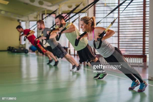 Grupp av glada atletisk människor utövar på cirkelträning på gymmet.