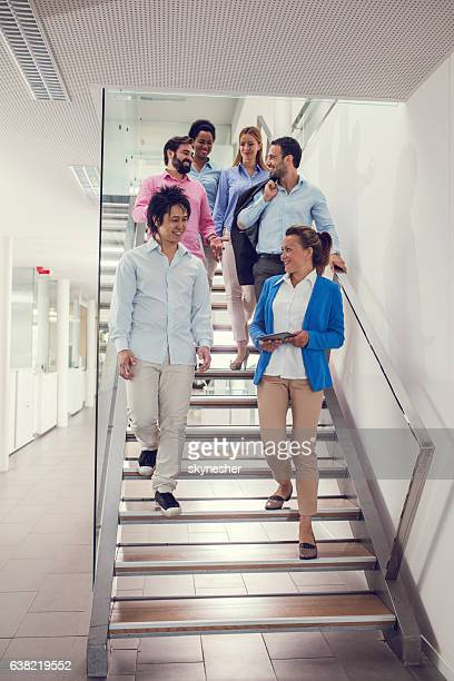 Group of happy business people walking down the stairs.