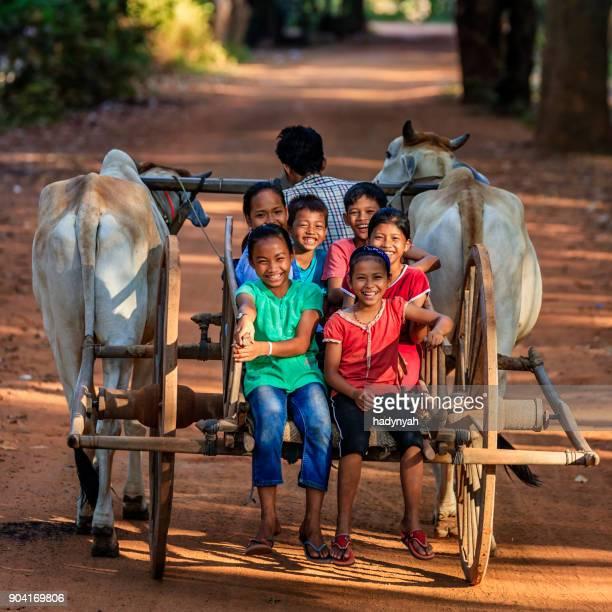 gruppe von glückliche kambodschanische kinder reiten ochsenkarren, kambodscha - ox cart stock-fotos und bilder
