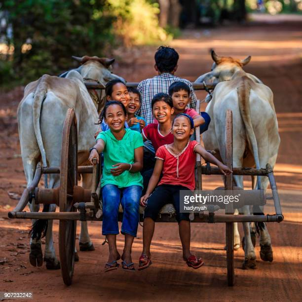 Group of happy Cambodian children riding ox cart, Cambodia