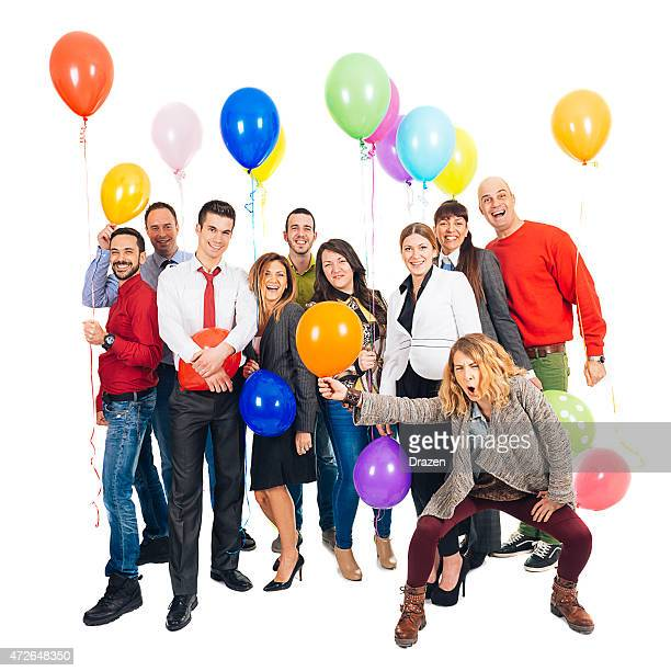 Group of happy casual and business people with helium balloons