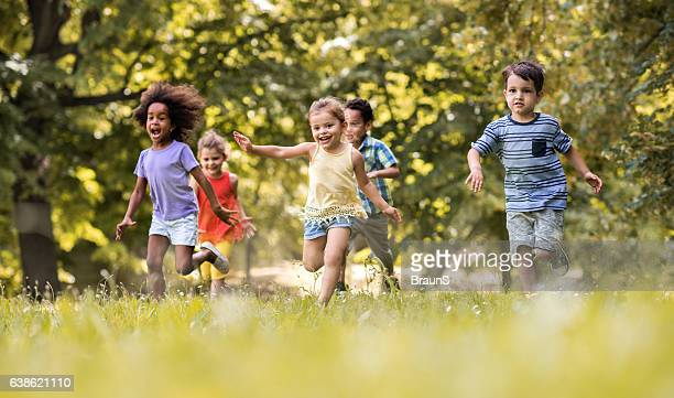 Group of happy children having fun while running in nature.