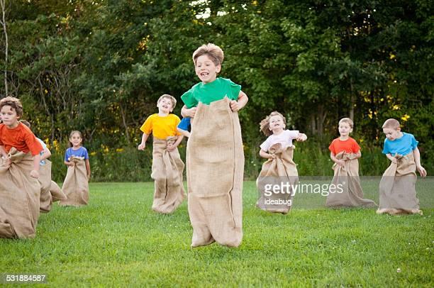 Groupe d'enfants heureux à l'extérieur des Course en sac de pommes de terre