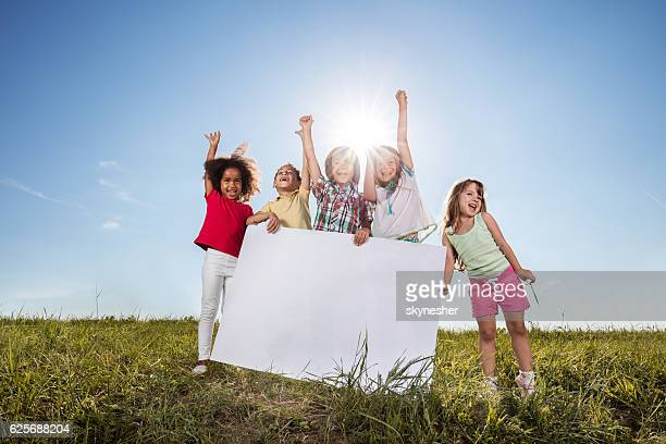 Group of happy children in a meadow holding white placard.