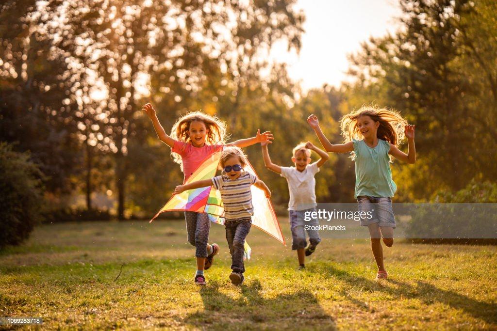 Gruppo di bambini felici che corrono nel parco pubblico : Foto stock